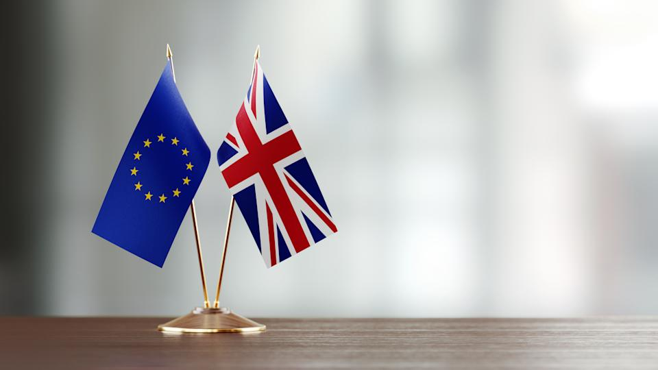 European Union and British flag pair on desk over defocused background. Horizontal composition with copy space and selective focus.