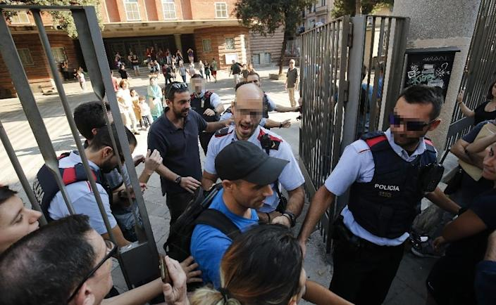 Police officers tried to stop pro-referendum supporters from entering the Collaso i Gil school in Barcelona (AFP Photo/PAU BARRENA)