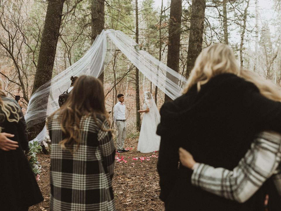 guests standing in front of a bride and groom getting married in a forest