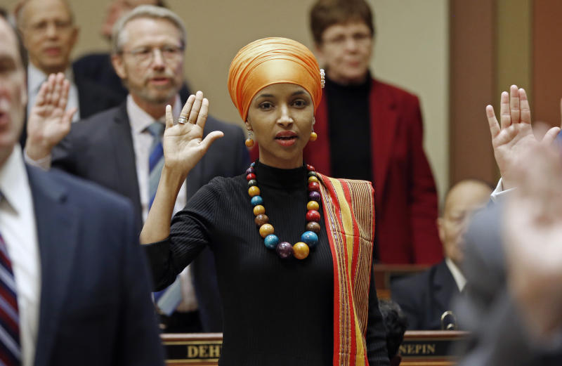 FILE - In this Tuesday, Jan. 3, 2017 file photo, State Rep. Ilhan Omar takes the oath of office as the 2017 legislature convened in St. Paul, Minn. Omar, a Muslim, is the nation's first Somali-American to be elected to a state legislature. Religion's role in politics and social policies is in the spotlight heading toward the midterm elections, yet relatively few Americans consider it crucial that a candidate be devoutly religious or share their religious beliefs, according to an AP-NORC national poll conducted Aug. 16-20, 2018. (AP Photo/Jim Mone)