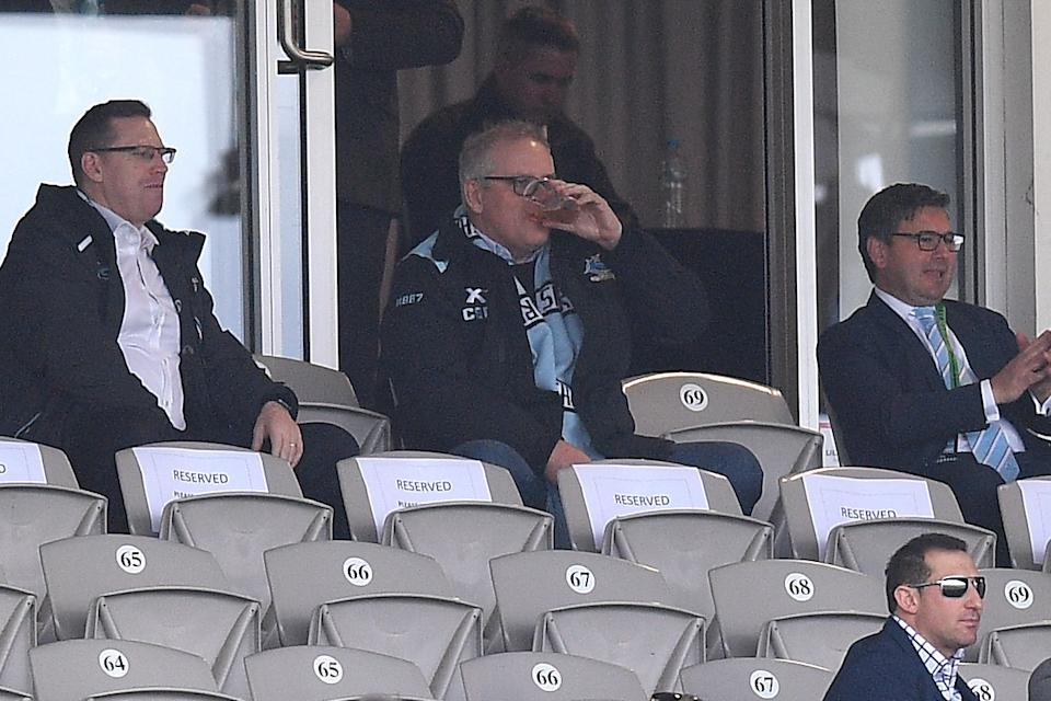 Prime Minister Scott Morrison sitting in the stands and drinking a beer while watching the Cronulla Sharks.