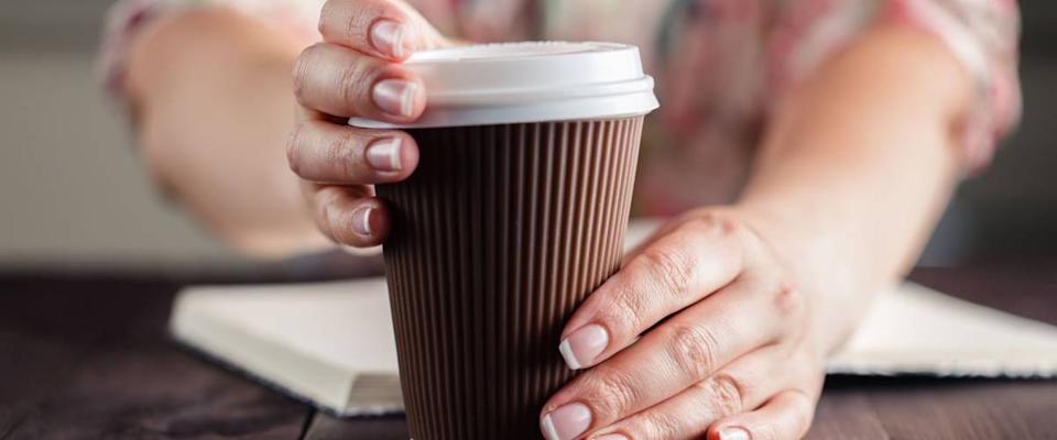 Woman holding takeout coffee at table and opening cup
