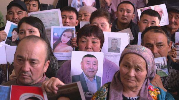 PHOTO: Families of the Uighur ethnic minority show pictures of their disappeared loved ones who have been sent to camps run by the Chinese government. (ABC)