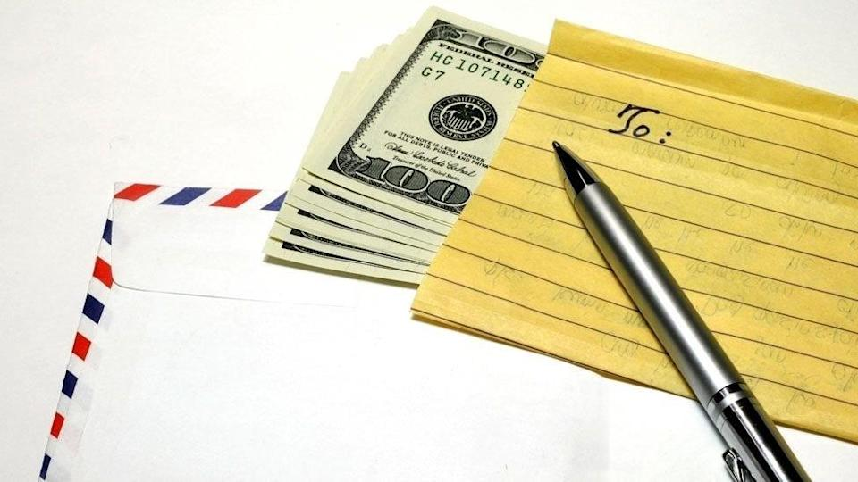 Envelope, US currency, notepaper and a pen