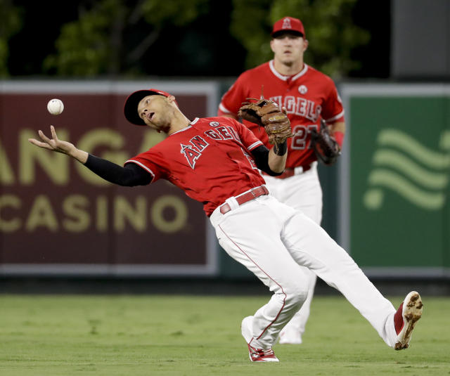 Los Angeles Angels shortstop Andrelton Simmons bare-hands a fly ball hit by Cleveland Indians' Jay Bruce as center fielder Mike Trout watches during the first inning of a baseball game in Anaheim, Calif., Wednesday, Sept. 20, 2017. (AP Photo/Chris Carlson)