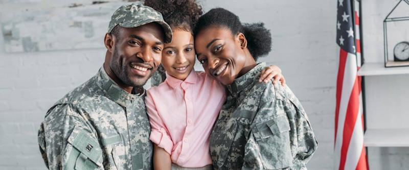 African american female and male soldiers embracing their daughter
