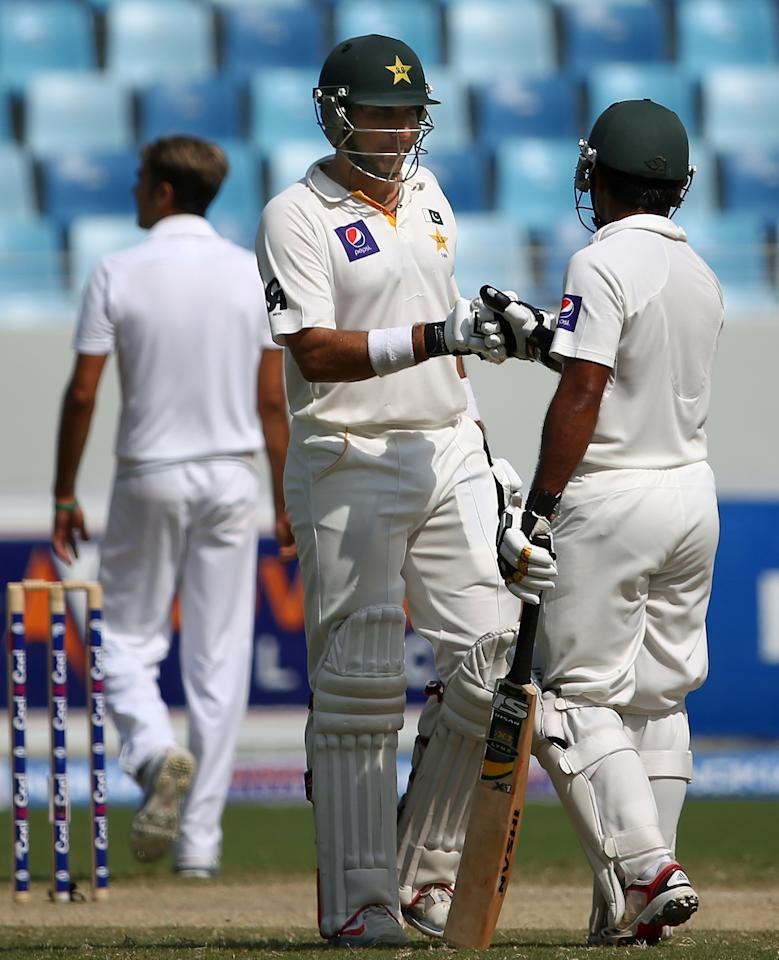 Pakistani batsman Misbah Ul Haq (L) receives congratulation from his teammate Asad Shafiq after scoring a 50 run during the fourth day of the second Test cricket match between Pakistan and South Africa in Dubai on October 26, 2013. AFP PHOTO/MARWAN NAAMANI        (Photo credit should read MARWAN NAAMANI/AFP/Getty Images)