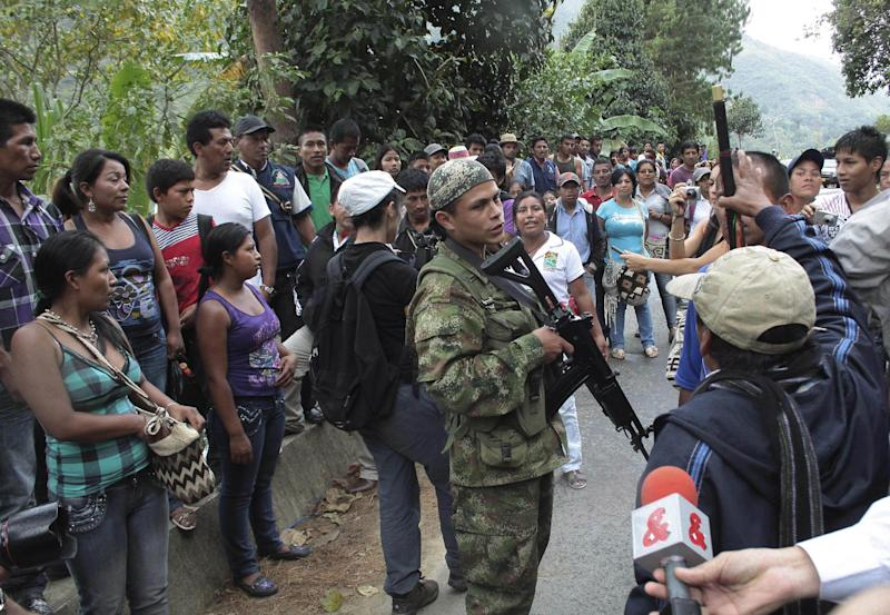 Indians surround a rebel of the Revolutionary Armed Forces of Colombia, FARC, on the outskirts of Toribio, southern Colombia, Wednesday, July 11, 2012. Rebels set up a roadblock on a road leading to Toribio while Colombia's President Juan Manuel Santos was holding a meeting with cabinet members and local authorities in the church of the town, that was attacked by guerrillas last week. (AP Photo/Juan Bautista Diaz)