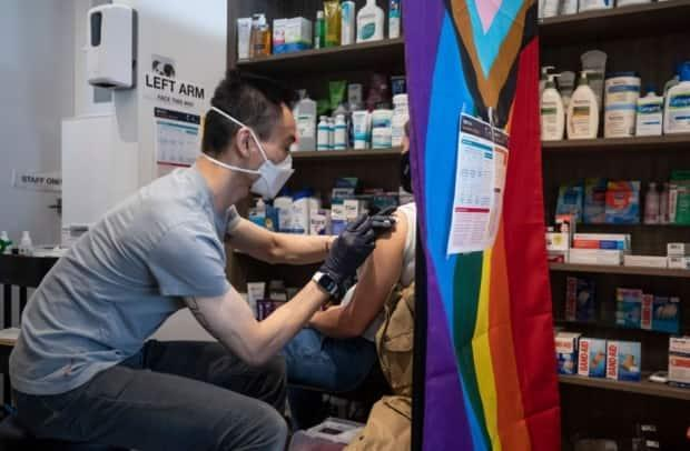 Pharmacist Eugene Woo delivers an AstraZeneca-Oxford vaccine at Davie Pharmacy in Vancouver, B.C. on Tuesday. (Ben Nelms/CBC - image credit)