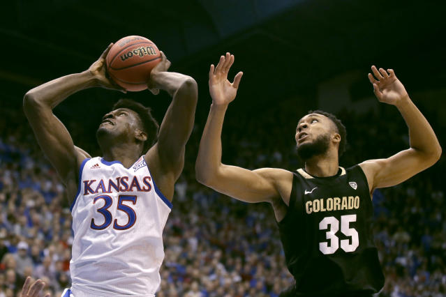 Kansas' Udoka Azubuike gets past Colorado's Dallas Walton to shoot during the first half of an NCAA college basketball game Saturday, Dec. 7, 2019, in Lawrence, Kan. (AP Photo/Charlie Riedel)