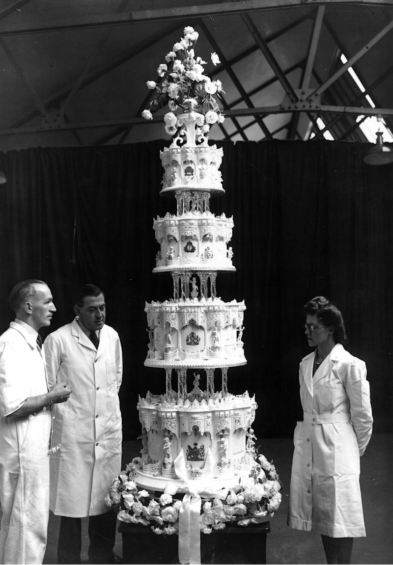 "Confectioners stand next to the impressive official cake, which stood <a href=""https://www.royal.uk/70-facts-about-queen-and-duke-edinburghs-wedding"" target=""_blank"">nine feet tall</a>."
