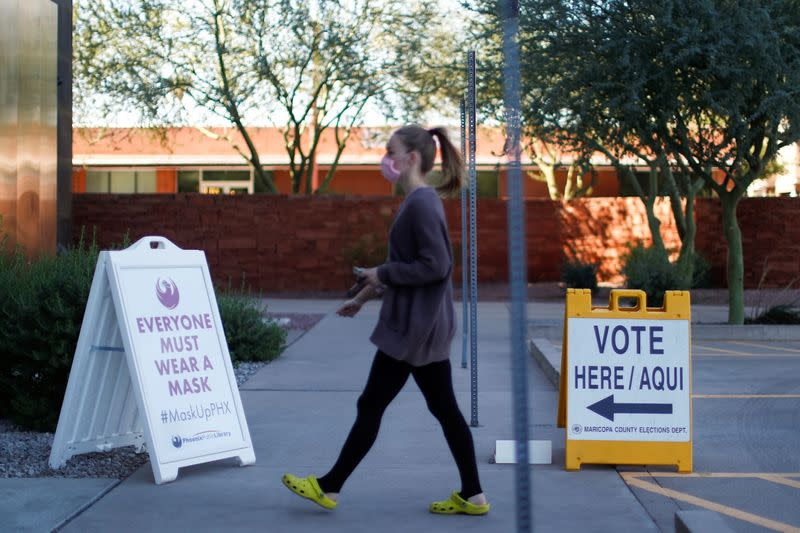A woman walks to cast her ballot at the register of voters during early voting in Phoenix, Arizona