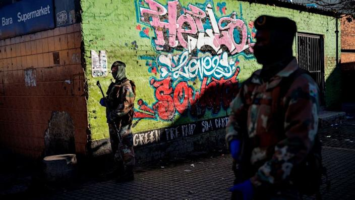 All but the highest risk sectors of the economy are allowed to reopen in South Africa and in Soweto soldiers patrol a market on Monday.