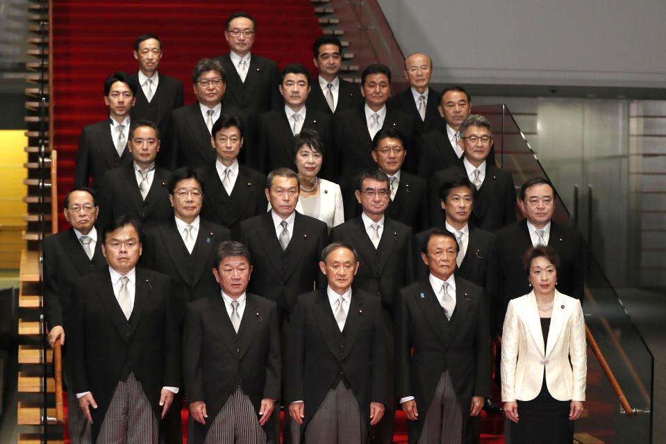FILE - In this Sept. 16, 2020, file photo, Japan's Prime Minister Yoshihide Suga, front center, and his cabinet ministers pose for a photo session at Suga's official residence in Tokyo. Japan especially lags in women's advancement in politics. Women account for less than 10% of lawmakers in the more powerful of its two-chamber parliament. About 40% of local assemblies have no female members or only one. Suga's 20-member Cabinet has only two female ministers, Olympic Minister Seiko Hashimoto, bottom right, and Justice Minister Yoko Kamikawa, center at third row from front. (Issei Kato/Pool Photo via AP, File)