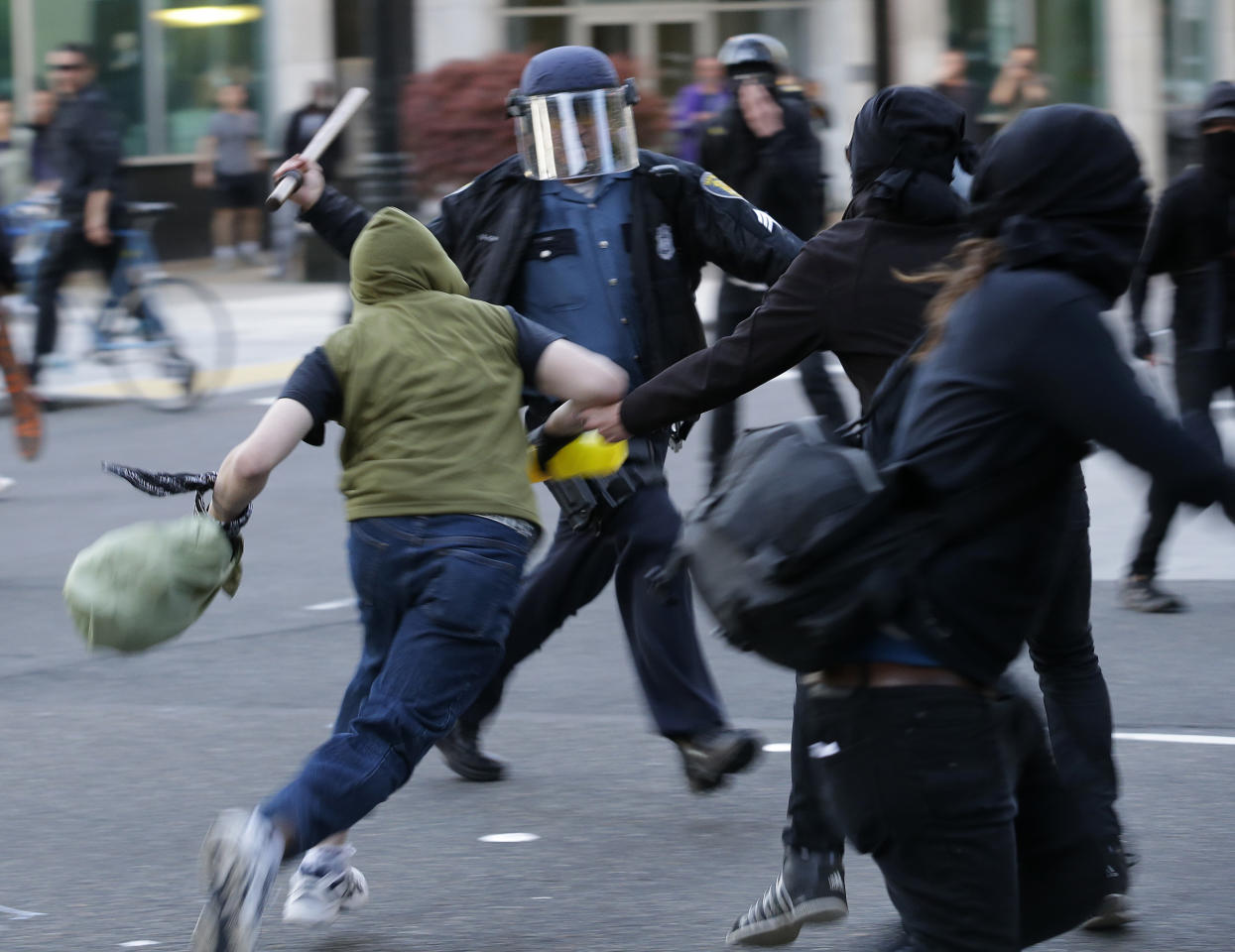 A Seattle Police officer swings his baton at protesters during a May Day march that began as an anti-capitalism protest and turned into demonstrators clashing with police, Wednesday, May 1, 2013, in downtown Seattle. (AP Photo/Ted S. Warren)
