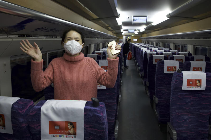 A passenger wearing a face mask to protect against the spread of new coronavirus talks about how happy she is to leave her 76-day stay in lockdown in Wuhan as she boards the first high-speed train to leave Hankou train station after the resumption of train services in Wuhan in central China's Hubei Province, Wednesday, April 8, 2020. After 11 weeks of lockdown, the first train departed Wednesday morning from a re-opened Wuhan, the origin point for the coronavirus pandemic, as residents once again were allowed to travel in and out of the sprawling central Chinese city. (AP Photo/Ng Han Guan)