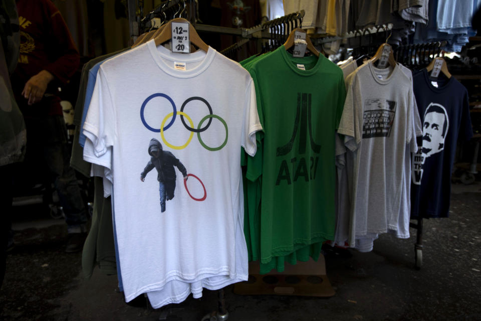 In this photo taken Monday, July 16, 2012, a t-shirt depicting a rioter holding an Olympic ring is displayed on sale in a London market. The guardians of the games are vigilant about protecting the integrity - and the commercial clout - of the Olympic brand. But even they can't stop the irreverent spirit of artists and craftspeople, who have responded to the games with a cheeky mix of celebration, skepticism and satire. (AP Photo/Matt Dunham)