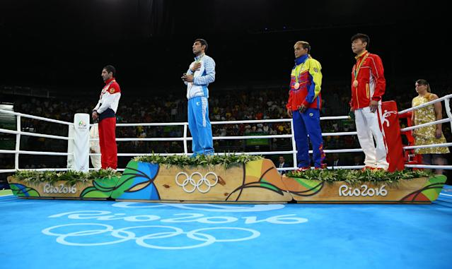 2016 Rio Olympics - Boxing - Victory Ceremony - Men's Fly (52kg) Victory Ceremony - Riocentro - Pavilion 6 - Rio de Janeiro, Brazil - 21/08/2016. (From L) Silver medallist Misha Aloian (RUS) of Russia, gold medallist Shakhobidin Zoirov (UZB) of Uzbekistan and bronze medallists Yoel Finol (VEN) of Venezuela and Hu Jianguan (CHN) of China stand at attention during the playing of the national anthem. REUTERS/Peter Cziborra FOR EDITORIAL USE ONLY. NOT FOR SALE FOR MARKETING OR ADVERTISING CAMPAIGNS.