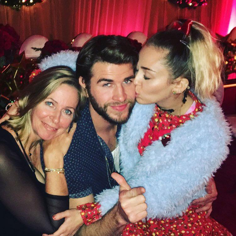 Liam Hemsworth Gets A Christmas Kiss From Fiancee Miley