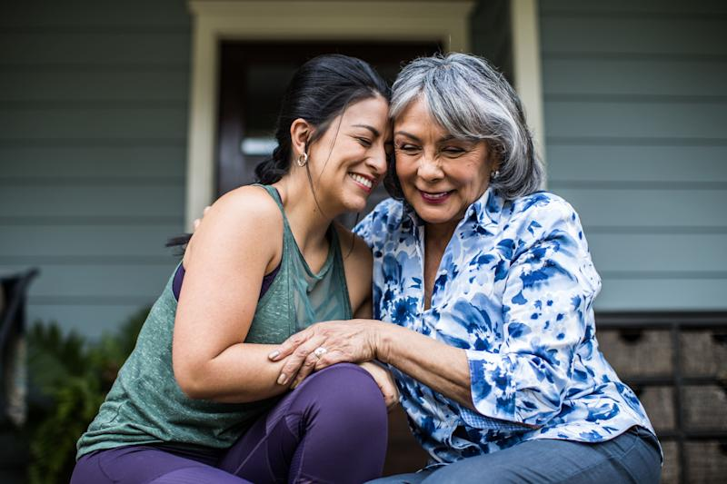 Senior woman and adult daughter laughing on porch