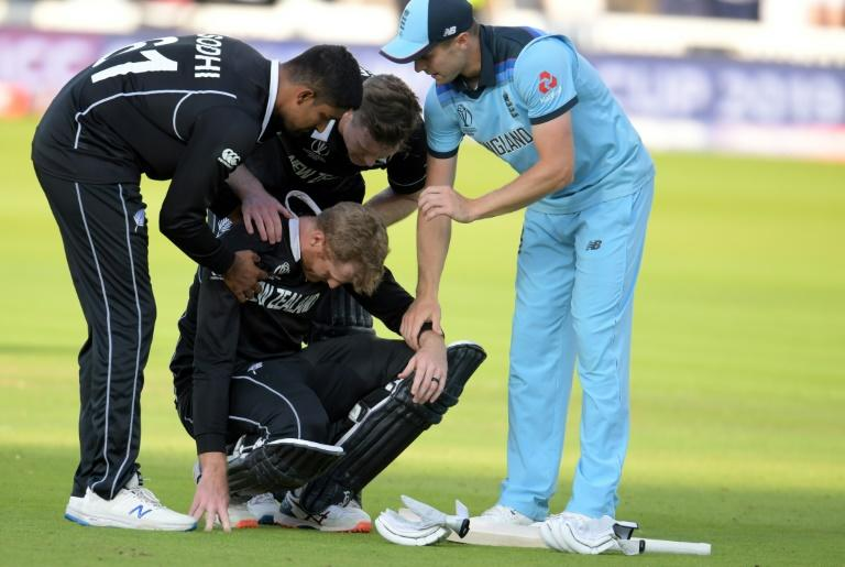New Zealand's Martin Guptill is consoled by teammates and England's Chris Woakes after losing the World Cup final