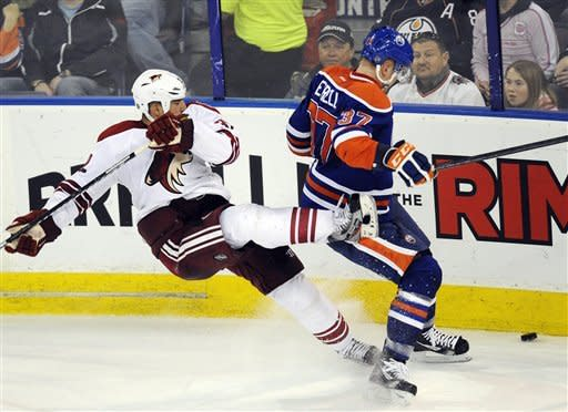 Edmonton Oilers' Lennart Petrell, right, knocks down Phoenix Coyotes' Michal Rozsival during the second period of an NHL hockey game in Edmonton, Alberta, on Sunday, March 18, 2012. (AP Photo/The Canadian Press, John Ulan)
