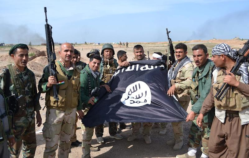 Iraqi Kurdish peshmerga fighters hold an Islamic State group flag in Sultan Mari, Iraq on March 9, 2015, after they reportedly re-took the area from IS jihadists (AFP Photo/Marwan Ibrahim)
