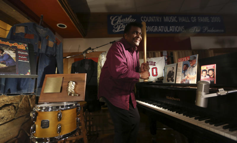 Country music legend Charley Pride jokes around with a bat among other items he is donating to the Smithsonian during an interview at his recording studio in Dallas, Texas, Monday, Sept. 24, 2012. The Smithsonian has selected Pride to be part of the new National Museum of African American History and Culture opening in 2015 with Pride giving the museum items from his life. (AP Photo/LM Otero)