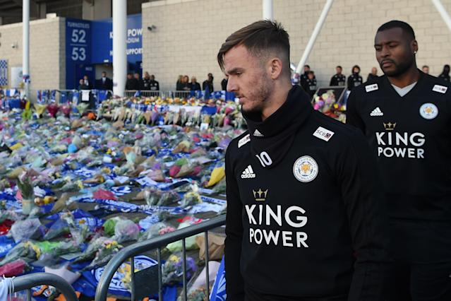 English midfielder James Maddison (L) and Leicester City's English-born Jamaican defender Wes Morgan (R) look at the floral tributes (Photo by Mike Egerton/PA Images via Getty Images)
