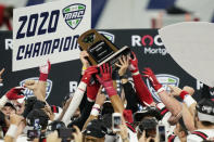 Ball State players reach for the trophy after defeating Buffalo in the Mid-American Conference championship NCAA college football game, Friday, Dec. 18, 2020, in Detroit. (AP Photo/Carlos Osorio)
