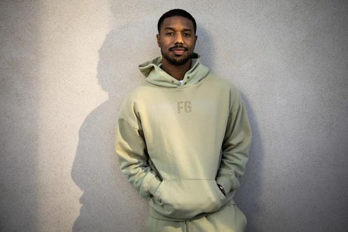 A man leaning against a white wall in a green hoodie