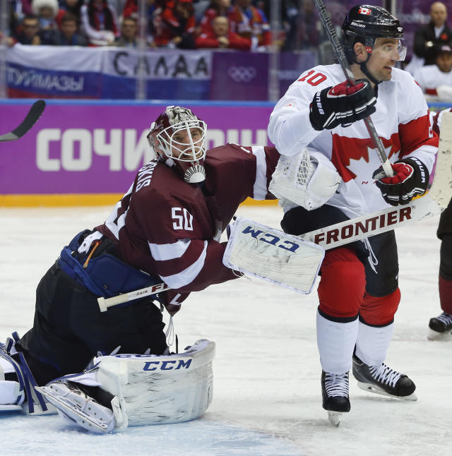 Latvia goaltender Kristers Gudlevskis, left, clears out Canada forward Patrick Sharp from the crease during the second period of a men's quarterfinal ice hockey game at the 2014 Winter Olympics, Wednesday, Feb. 19, 2014, in Sochi, Russia. (AP Photo/Julio Cortez)