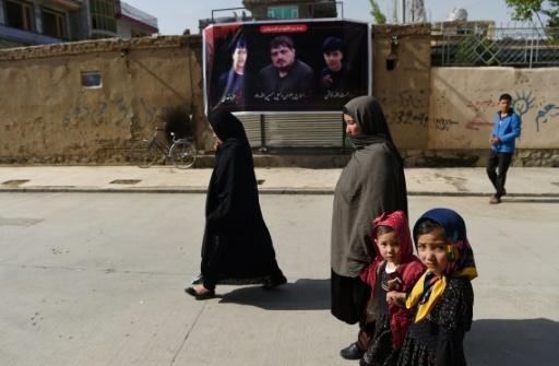 People walk past a banner bearing the image of Wakil Hussain Allahdad, 32, one of the 57 victims of a suicide blast on a voter registration centre in Kabul, in the city on April 23, 2018