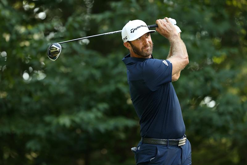 Dustin Johnson watches a shot with his club behind his head.