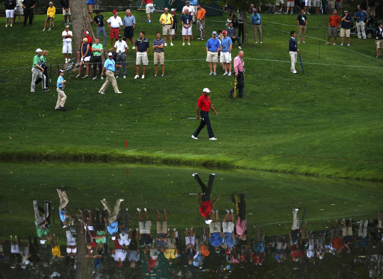 Tiger Woods of the U.S. is reflected in a pond as he walks along the third hole as he and teammate Matt Kuchar play against International team members Adam Scott of Australia and Hideki Matsuyama of Japan in their four ball match at the 2013 Presidents Cup golf tournament at Muirfield Village Golf Club in Dublin, Ohio October 5, 2013. REUTERS/Jeff Haynes (UNITED STATES - Tags: SPORT GOLF TPX IMAGES OF THE DAY)