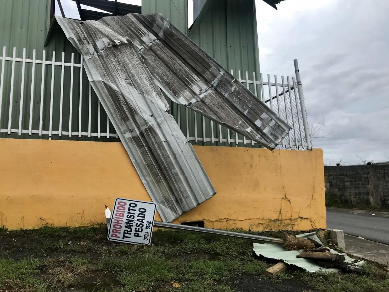 """A downed """"no trespassing"""" sign lays on the grass in front of a building damaged by Hurricane Maria in Bayamón, Puerto Rico. (Photo: Caitlin Dickson/Yahoo News)"""