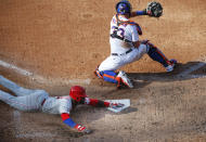 Philadelphia Phillies' Rhys Hoskins, bottom, beats the throw to New York Mets catcher James McCann (33) for a run during the sixth inning of a baseball game Saturday, June 26, 2021, in New York. (AP Photo/Noah K. Murray)