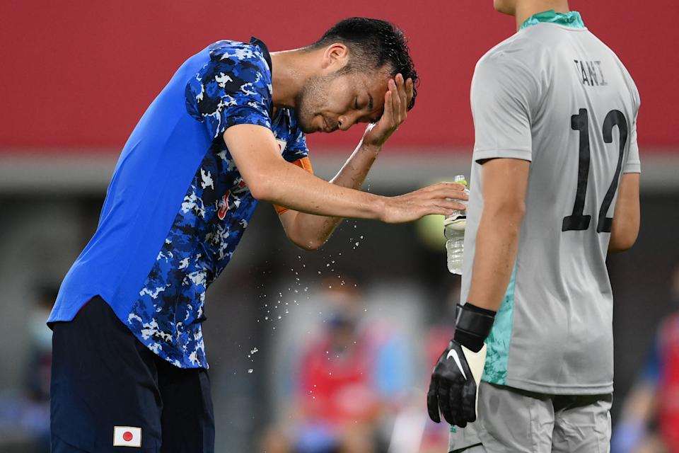 <p>Japan's defender Maya Yoshida cools himself off during the Tokyo 2020 Olympic Games men's group A first round football match between Japan and South Africa at Tokyo Stadium in Tokyo on July 22, 2021. (Photo by FRANCK FIFE / AFP)</p>