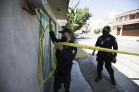 A police officer marks a security perimeter around the house where bones were found under the floor in the Atizapan municipality of the State of Mexico, Thursday, May 20, 2021. Police have turned up bones and other evidence under the floor of the house where a man was arrested for allegedly stabbing a woman to death and hacking up her body. (AP Photo/Fernando Llano)