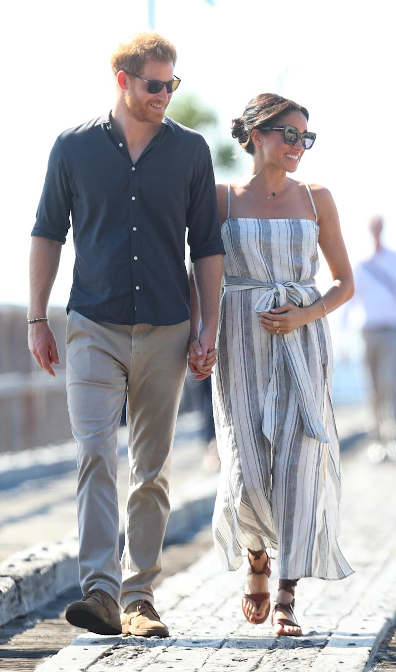 Meghan, Duchess of Sussex seen holding her baby bump whilst Prince Harry, Duke of Sussex and Meghan, Duchess of Sussex walk along a wharf in Kingfisher bay on October 22, 2018 in Fraser Island, Australia. The Duke and Duchess of Sussex are on their official 16-day Autumn tour visiting cities in Australia, Fiji, Tonga and New Zealand.