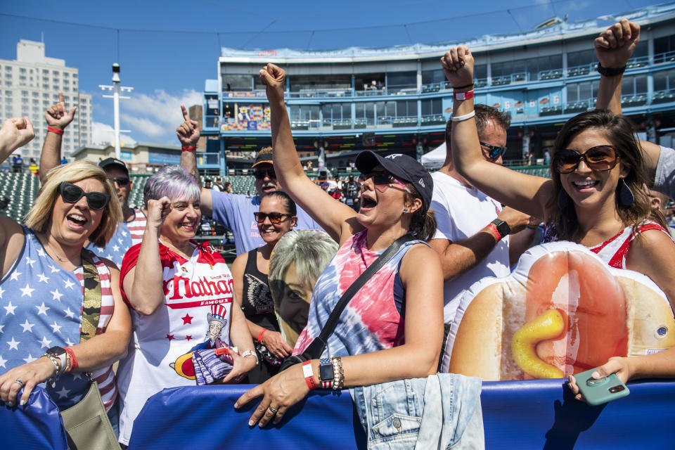 Fans cheer on contestant Larell Marie Mele, left, before going onstage at the Nathan's Famous Fourth of July International Hot Dog-Eating Contest in Coney Island's Maimonides Park on Sunday, July 4, 2021, in the Brooklyn borough of New York. (AP Photo/Brittainy Newman)