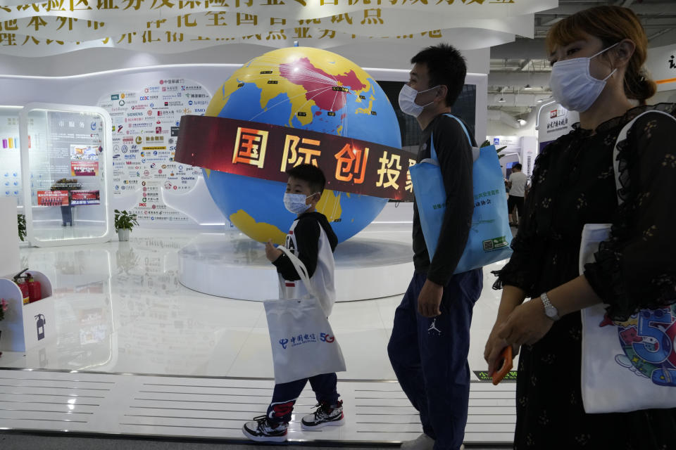 Visitors walk by a globe depicting the reach of China's financial services around the world during the China International Fair for Trade in Services (CIFTIS) in Beijing, China, Monday, Sept. 6, 2021. The ruling Communist Party's campaign to tighten control over China's industries and reduce use of foreign technology is slashing economic growth, a foreign business group warned Thursday, Sept. 22 and it appealed to Beijing to reverse course and open state-dominated markets wider. (AP Photo/Ng Han Guan)