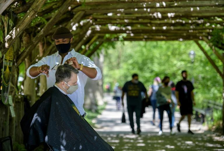 Barber Herman James cuts a client's hair under a pergola in Central Park on May 6, 2021, in New York City
