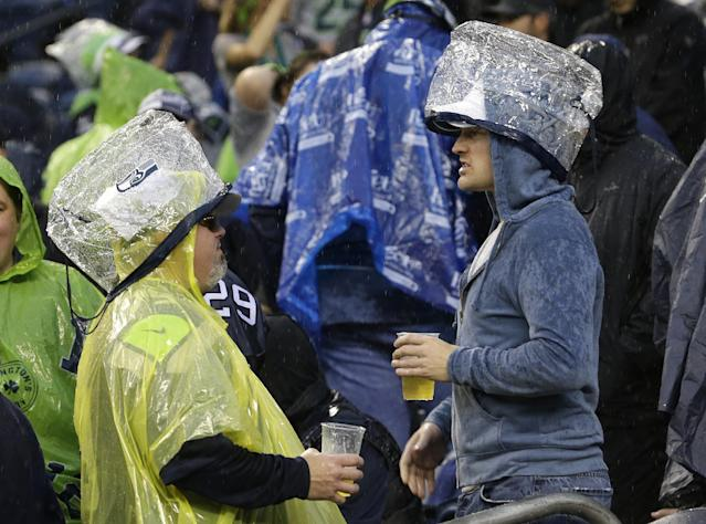 Seattle Seahawks fans wear official approved NFL security bags as rain covers during a severe weather delay in the first half of an NFL football game between the Seattle Seahawks and the San Francisco 49ers Sunday, Sept. 15, 2013, in Seattle. (AP Photo/Elaine Thompson)