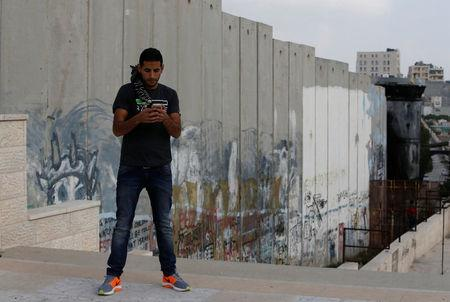 Nuseir Yassin uses his mobile phone as he stands near a section of the Israeli barrier in Aida refugee camp in the West Bank city of Bethlehem March 2, 2017. REUTERS/Mussa Qawasma