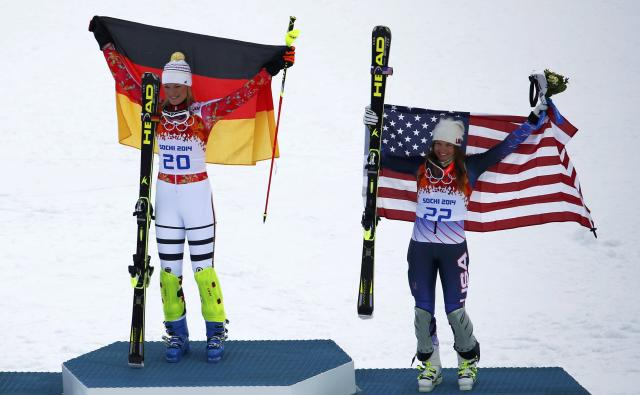 Winner Germany's Maria Hoefl-Riesch (L) and third-placed Julia Mancuso of the U.S. hold up their flags on the podium during the victory ceremony after the women's alpine skiing super combined event at the 2014 Sochi Winter Olympics at the Rosa Khutor Alpine Center February 10, 2014. REUTERS/Dominic Ebenbichler (RUSSIA - Tags: SPORT SKIING OLYMPICS)