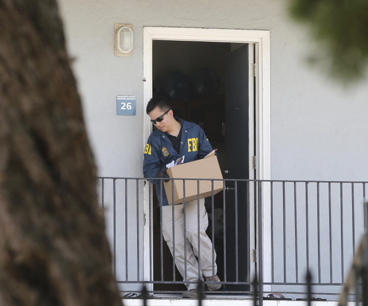 A federal agent removes items from an apartment following the arrest of Omar Ameen, Wednesday, Aug. 15, 2018, in Sacramento, Calif. Ameen, a 45-year-old Iraqi refugee, was arrested on a warrant alleging that he killed an Iraqi policeman in 2014 while serving with the Islamic State terror organization. (AP Photo/Rich Pedroncelli)