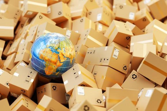 A globe surrounded by cardboard parcels.