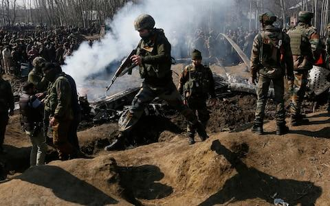 Indian army soldiers arrive near the wreckage of an Indian aircraft after it crashed in Budgam area - Credit: Mukhtar Khan/AP