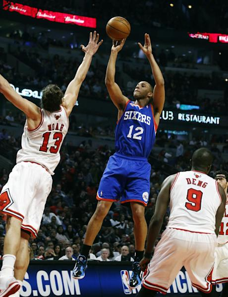 Philadelphia 76ers forward Evan Turner (12) shoots over Chicago Bulls' Joakim Noah (13) and Luol Deng (9) during the first half of an NBA basketball game, Thursday, Feb. 28, 2013, in Chicago. (AP Photo/Charles Rex Arbogast)